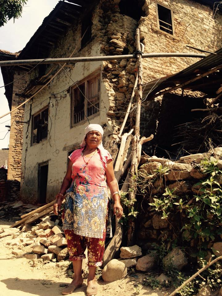 Krishna's mother in front of their massively damaged house